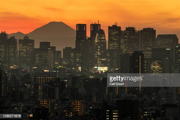 Mount Fuji is seen behind the city skyline at dusk on December 23, 2020 in Tokyo, Japan. The Tokyo Metropolitan Government announced 748 new cases of...