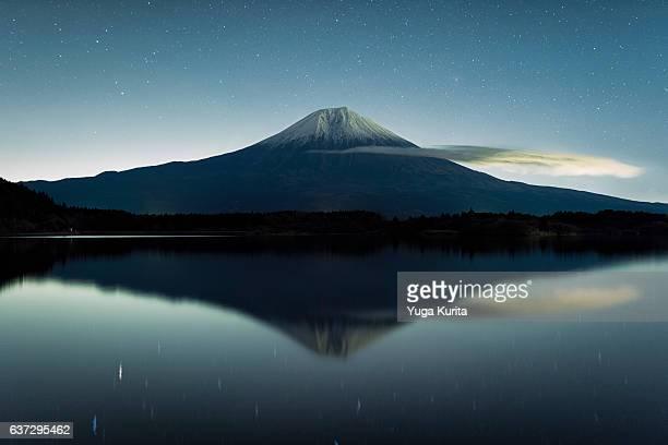 mount fuji reflected in lake tanuki at night - marderhund stock-fotos und bilder