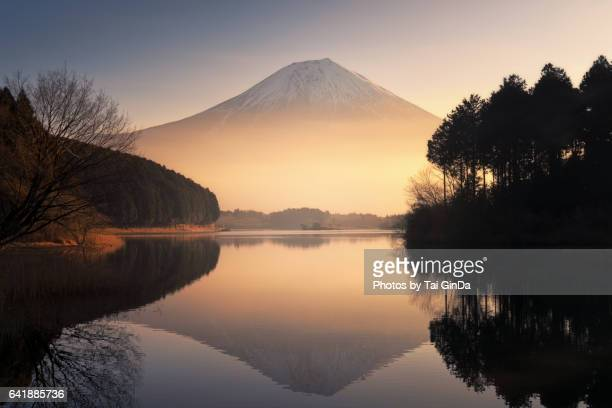 Mount Fuji reflected in Tanuki Lake with golden mist