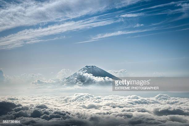 mount fuji rising above the clouds - mount fuji stock photos and pictures