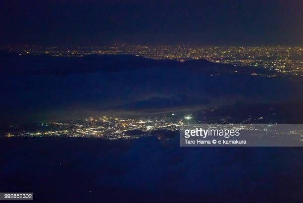 mount hakone, suruga bay, mishima and numazu cities in shizuoka prefecture and hiratsuka city in kanagawa prefecture in japan night time aerial view from airplane - mishima city stock photos and pictures