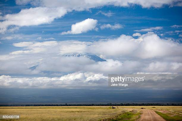 mount kilimanjaro seen through clouds in tanzania - jake warga fotografías e imágenes de stock
