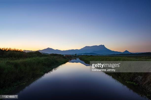 mount kinabalu view at sunrise from farm water irrigation canal - 運河 ストックフォトと画像