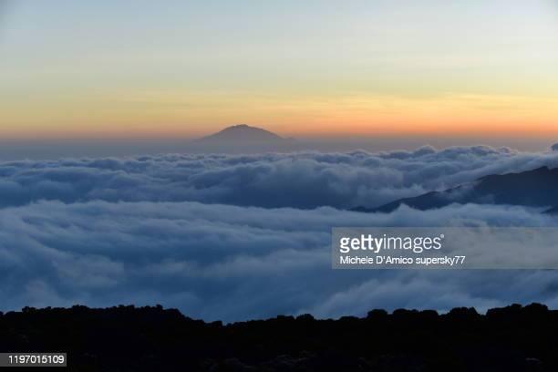 mount meru above the fog layer at dusk - meru filme stock-fotos und bilder
