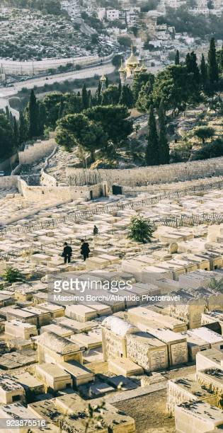 mount of olives, orthodox jews in the jewish cemetery, on the background the russian church of mary magdalene - mount of olives stock photos and pictures