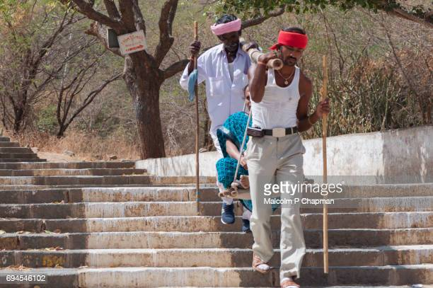 mount shatrunjaya, 'doolie' workers carry a jain pilgrim at holy site at palitana, gujarat - palitana stock photos and pictures