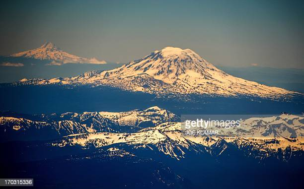 Mount St Helens backgrounded by Mount Hood is seen southeast of Seattle in the state of Washington United States on June 102013 AFP PHOTO/JOE KLAMAR