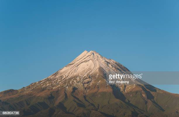 Mount Taranaki with snow cover on the peak in the first snow of winter season, New Zealand.