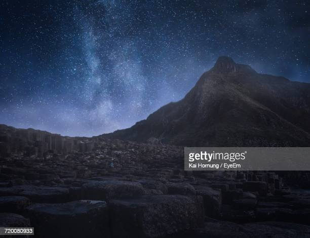 mountain against sky at night - giant's causeway stock pictures, royalty-free photos & images