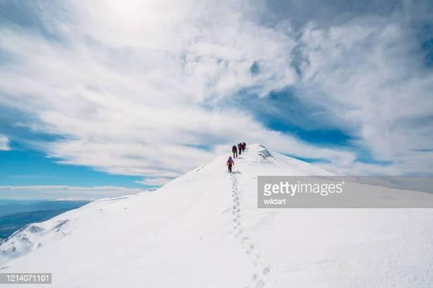 冬の高地山頂で連続して上に移動する山岳登山チーム - 冠雪 ストックフォトと画像