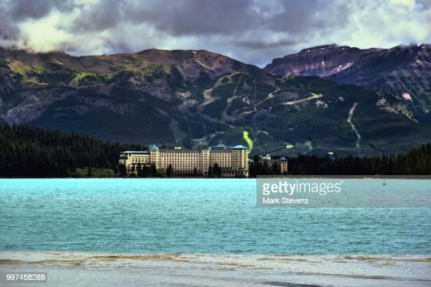 a mountain backdrop to the fairmont chateau lake louise - chateau lake louise ストックフォトと画像