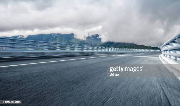 mountain background with clouds, dynamic city highway - empty road stock pictures, royalty-free photos & images