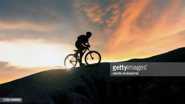 Mountain Bike cyclist cycling on the hill mountain twilight time on top of a mountain , Extreme sport concept.