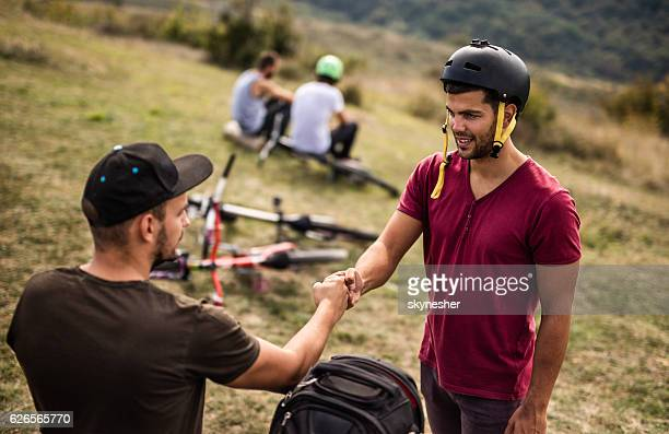 Mountain bike cyclist fist bumping with is friend in nature.