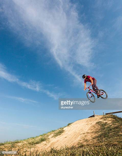 Mountain bike cyclist performing straight air jump over dirt hill.