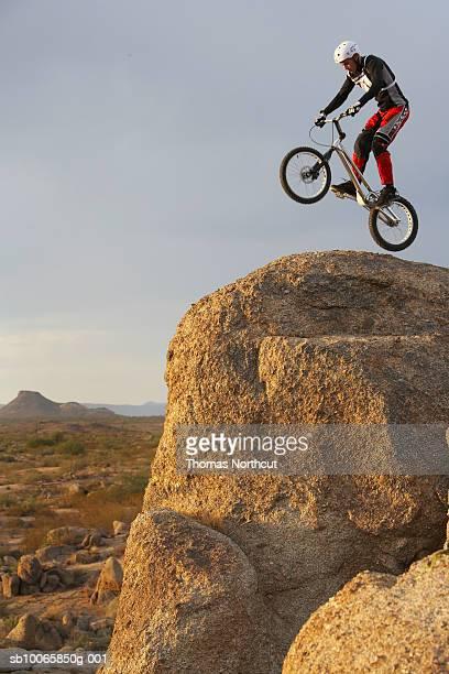 Mountain bike rider doing wheely on mountain peak, side view