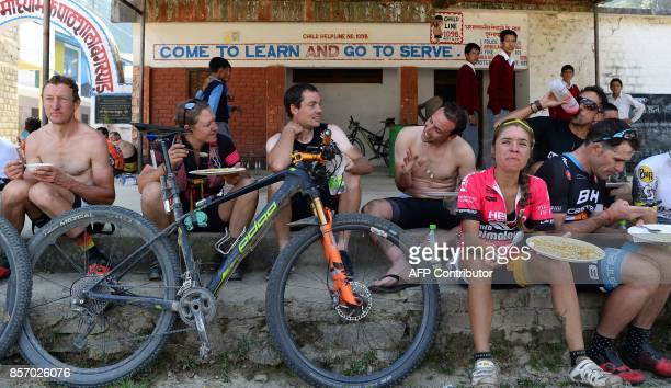 Mountain bike riders eat after competing in the Hero MTB Himalaya mountain bike race at the rest area in Bagshed about 50km from Mandi in the...