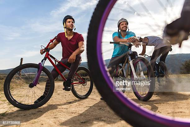Mountain bike riders relaxing on bicycles on dirt road.