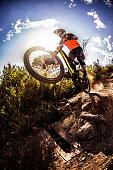 Mountain biker about to dirt jump over rough terrain