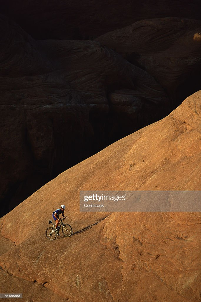 Mountain biker ascending rock formation , Moab , Utah : Stockfoto
