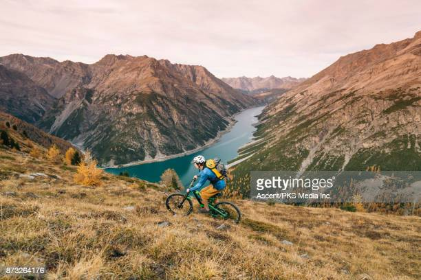 mountain biker ascends mountainous ridge crest, valley below - forza italia foto e immagini stock