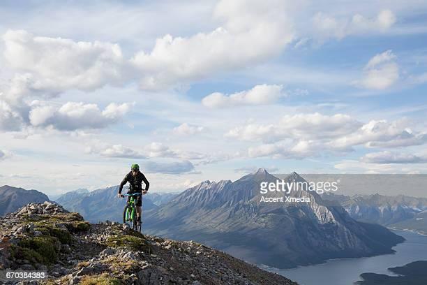 Mountain biker ascends to ridge crest above valley