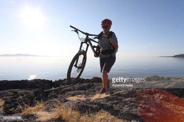 mountain biker carries bike over difficult terrain - escapism stock photos and pictures