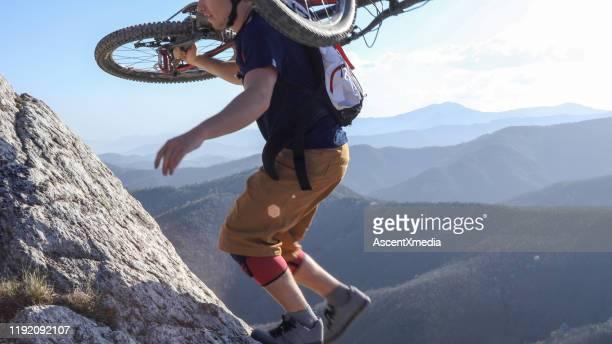 mountain biker porta la bici in cima alla scogliera - part of a series foto e immagini stock
