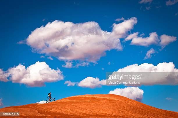 Mountainbiker Klettern auf glattem rock.