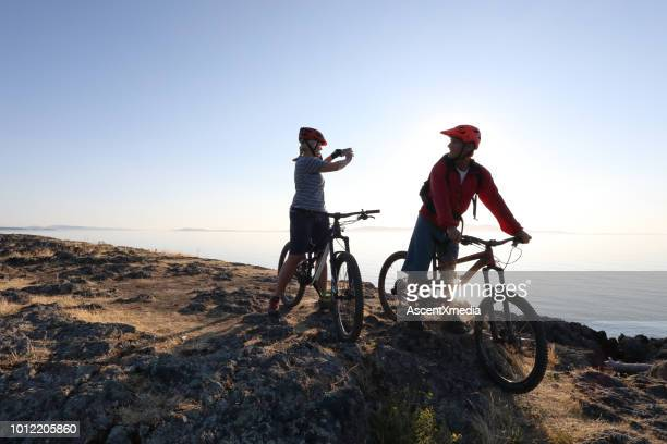 mountain biker couple take photo with smart phone - victoria canada stock pictures, royalty-free photos & images