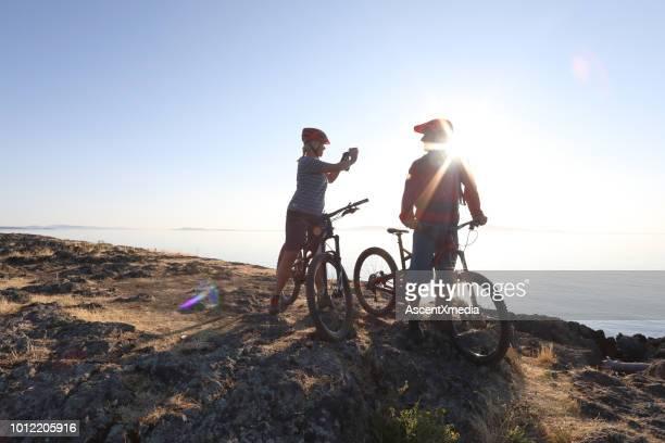 mountain biker paar neem foto met slimme telefoon - vancouver island stockfoto's en -beelden
