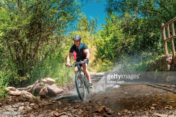 mountain biker crossing a river and splashing water in the forest - comunidad autónoma de castilla y león fotografías e imágenes de stock