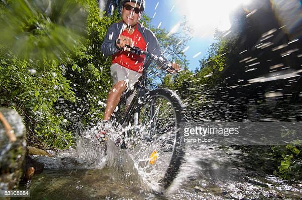Mountain biker crossing stream, splashing water, low angle view (blurred motion)