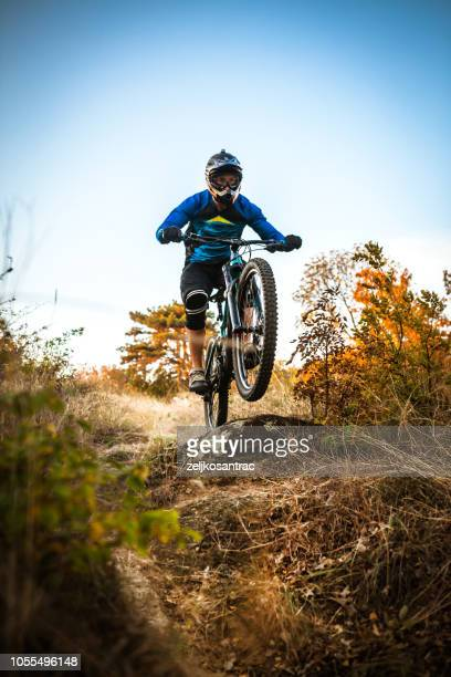 mountain biker cycling on trail in woods - mountain bike stock pictures, royalty-free photos & images