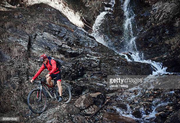 Mountain biker cycling over rocks