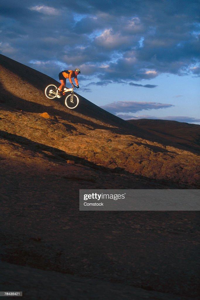 Mountain biker descending rock formation , Moab , Utah : Stockfoto