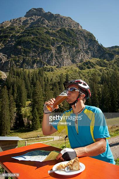 Mountain biker drinking a beer, Kleinwalsertal, Vorarlberg, Austria