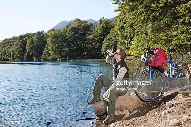 Mountain biker drinking by lake