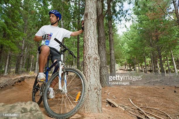 Mountain biker drinking water in forest