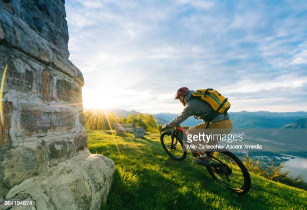 Mountain biker follows alpine track, traverses mountainside