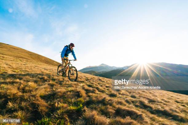 Mountain biker follows alpine track, traversing mountainside