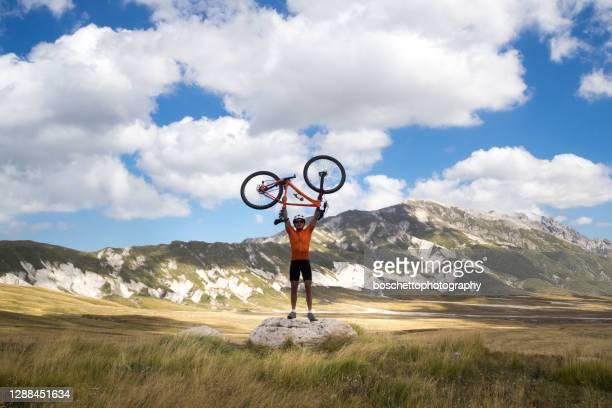 mountain biker che tiene la bici sopra la testa; scenografie sullo sfondo - campo imperatore foto e immagini stock