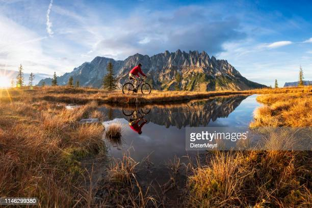 mountain biker in front of mountain lake in the alps - mount hochkönig - salzburger land stock pictures, royalty-free photos & images