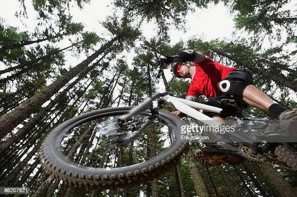 Mountain biker in mid-air in forest
