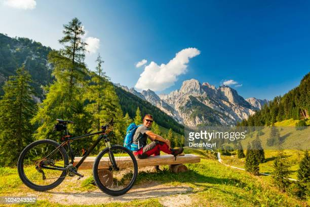mountain biker in the alps is taking a break on a bench - berchtesgaden stock pictures, royalty-free photos & images