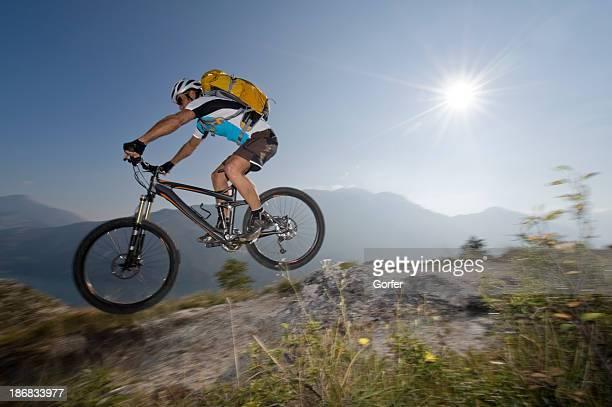 Mountain biker in the back light jumping