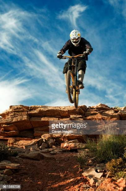 Mountain biker jumping from cliff against sky