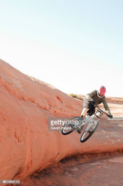 Mountain biker jumping from rock formation against clear sky