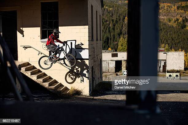 Mountain biker jumping out of abandoned building.