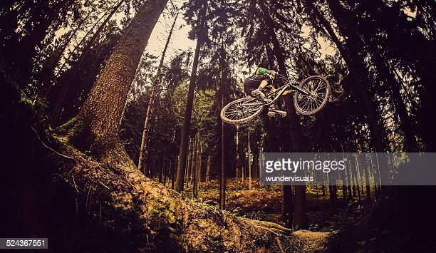 Mountain Biker Jumps In Forest